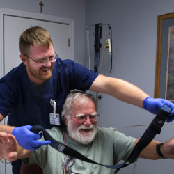 Sleep technician Jordan Qualey (left) helps Corky Potter with a belt that will monitor his chest movements while he is sleeping at the St. Joseph Healthcare Center for Sleep Medicine in Bangor.