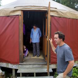 "Josh Wehrwein (right) holds the door to his family's canvas yurt while his wife, Melanie (center), and their daughter, Aria, 6, put on their shoes in Sedgwick on Wednesday. In October of 2010 the Wehrwein family began a journey out of suburbia and into ""imagined living"" in rural Maine. The family has been building a three-story wooden yurt on their property."
