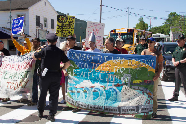 Protesters block Washington Street in Bath on Saturday morning before the christening of the future USS Michael Monsoor at Bath Iron Works.