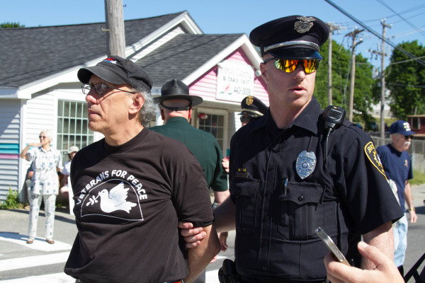 Bruce Gagnon of Bath is arrested Saturday morning on Washington Street, just outside Bath Iron Works. A crowd of more than 1,000 people gathered inside the shipyard for the christening of the future USS Michael Monsoor. Gagnon and 11 others were charged with obstructing a public way.