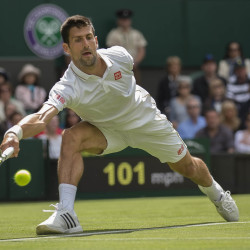 Novak Djokovic reaches to return a shot to James Ward in the opening match Monday at Wimbledon at the All England Lawn Tennis and Croquet Club.