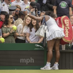 Serena Williams takes a selfie with a spectator after her match against Amra Sadikovic on day two of Wimbledon Tuesday at the All England Lawn Tennis and Croquet Club.