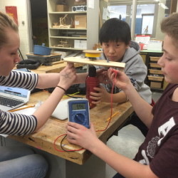 Eighth-graders (from left) Sydni Moores, Joshua Chun and Vincent Bonarrigo work at the Troy Howard Middle School in Belfast on a model merry-go-round that will generate electricity. They are part of Team Power Play, which recently won first place in Maine as part of the national eCYBERMISSION competition.