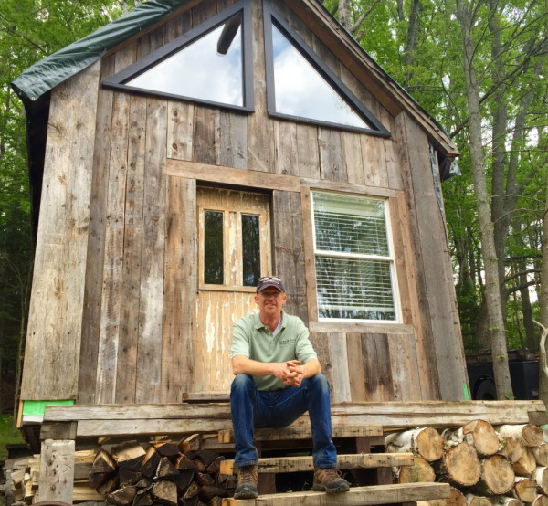 Wood salvager Ryan Deane sits outside his cabin made of reclaimed Maine wood from buildings, barns and houses across the state.