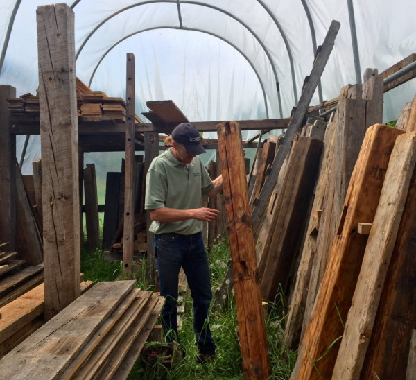 Wood salvager Ryan Deane inspects reclaimed beams in the lumber yard at  Down and Back Wood - How One Man Is Making A Career Out Of Foraging Old Maine Wood
