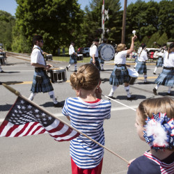Mariah Pardos, 10, (center) and Kennedy Stanley, 8, watch the Fourth of July parade on Monday in Brewer.