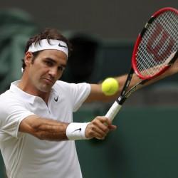 Switzerland's Roger Federer returns a shot to USA's Steve Johnson during their Wimbledon singles match Monday.