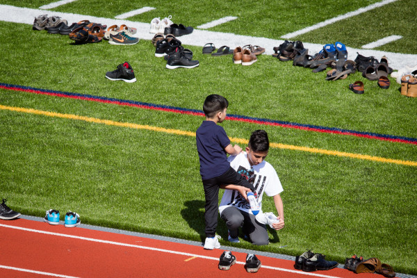A boy gets help removing his shoes before praying at Fitzpatrick Stadium in Portland on Wednesday, marking the end of Ramadan.