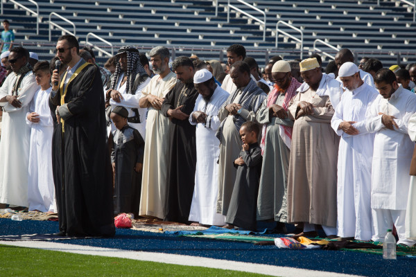 Men bow their heads facing east while Imam Younus Alfayyadh leads the prayers at Fitzpatrick Stadium in Portland on Wednesday as local Muslims celebrated Eid al-Fitr.