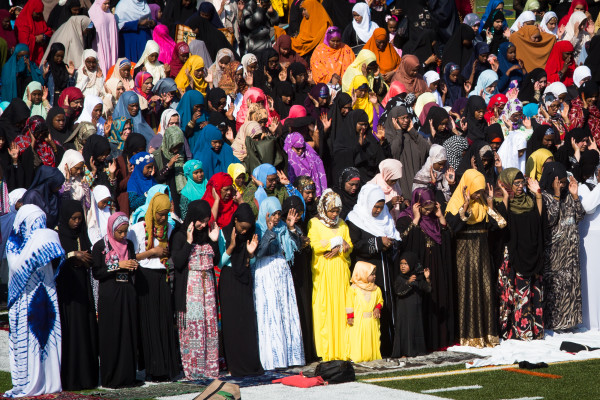 Local Muslim women dressed in colorful clothes stand on the football field at Fitzpatrick Stadium in Portland on Wednesday morning while praying and celebrating the end of the holy month of Ramadan.