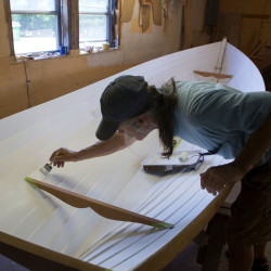 Dale Cottrell paints a Penobscot wherry on July 1 in his shop, Cottrell Boatbuilding, in Searpsort.
