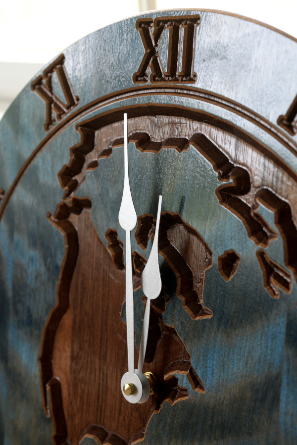 An earth clock made made by Tamzin Higgins features a walnut back and flamed birch on top.