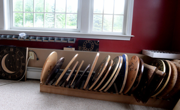 Different hardwood clocks made by Tamzin Higgins are stacked up in her office.