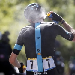 Team Sky rider Luke Rowe sprays sun screen on his neck as he cycles during the sixth stage Thursday from Arpajon-sur-Cere to Montauban, France.