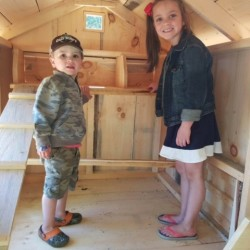 Six-year-old Kendall Killam (right) of Monson stands inside her new chicken coop with her little brother, Kyle Killam. Kendall just won the coop and six chickens in a statewide coop giveaway organized by the Maine Poultry Connection resource group.
