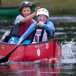 Tommy Owen and Noah Kreutz give it their all to finish during the Open Canoe youth race of the Penobscot River Whitewater Nationals Regatta on Thursday. The race began in Orono and ended in Veazie.