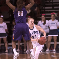 The University of Maine's Liz Wood (right) drives past Albany's Zakiya Saunders during their game in Bangor on March 2.