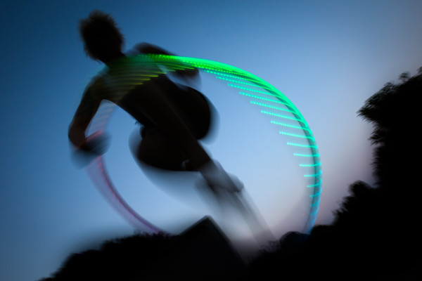 Leaping through a lighted hoop in Augusta, flow artist Alexis Powers practices her craft in her back yard at dusk.