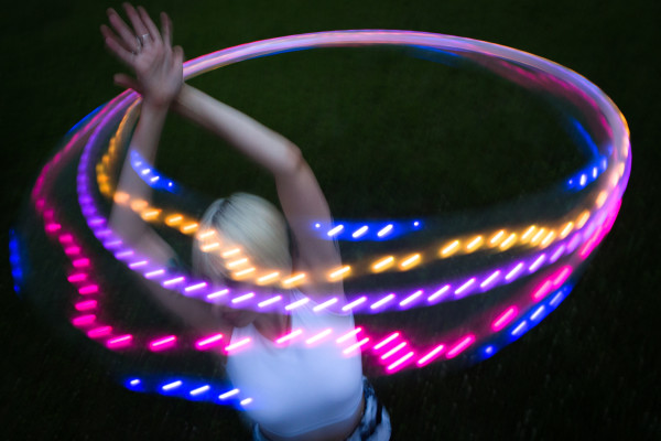 A lighted hoop changes colors as flow artist Alexis Powers spins it over her head at dusk in her back yard in Augusta. Powers is a graduate of the Maine College of Art and had an extensive background in painting and drawing before taking up performance in 2009.