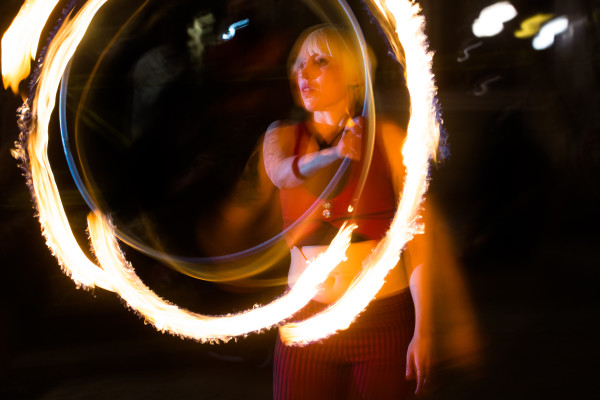 "Flow artist Alexis Powers spins a flaming hoop in Portland's Post Office Park as part of the July First Friday get-together hosted by Luminous Fire and Flow. ""&quotI'm trying to create these visual and fully-immersive images with the music, costume, makeup, lighting, choreography,""&quot Powers said."
