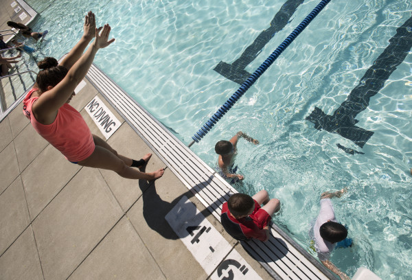 Swimming instructor Katie Plourde (left) gives children tips on stroke technique during swimmig lessons on July 11 at the Beth Pancoe Aquatic Center in Bangor.