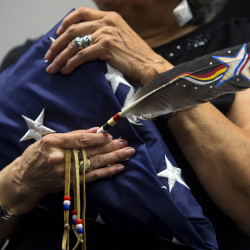 Sylvia Polchies holds an American Eagle feather and a folded American flag that she received on behalf of her late father, Henry Sockbeson, during a ceremony to honor six members of the Passamaquoddy Tribe who fought in World War I on Sunday in Indian Township.