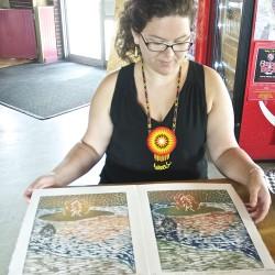 Penobscot artist Christiana Becker leafs through her portfolio of wood block prints.