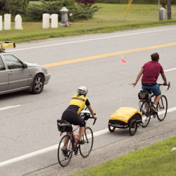 People ride their bicycles along Route 1 in Stockton Springs on Monday.