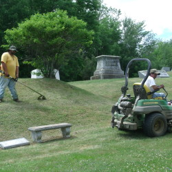 Ralph Boyington of Houlton mows the grass on a section of Evergreen Cemetery known as Angel's Hill while his colleague James Wallace trims nearby with a weed whacker on Friday, July 15, 2016. The two are a dedicated tag-team who carefully maintain municipal resting places with a sense of duty to the deceased while also caring for the needs of the living, according to Milton Cone, the town''s fire chief and cemetery superintendent. They are the unsung heroes in this place.""