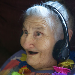 Kay Beal smiles and sings along while listing to a customized selection of music on her iPod on Tuesday in the common area at Narraguagus Bay Health Care in Milbrige. Beal is involved in the Music and Memory program aimed at tapping into the memories of people with dementia.