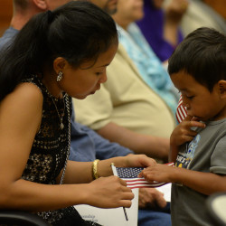 Eighteen people from 12 different countries became United States citizens on Friday at the Federal Building in Bangor. Before the start of the ceremony, Chan Nhao, originally from Cambodia, looks at an American flag with her 4-year-old son Ryson Meas.