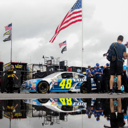 The car of NASCAR Sprint Cup Series driver Jimmie Johnson is reflected in a puddle of water near the garage area prior to the Pennsylvania 400 Sunday at Pocono Raceway in Long Pond, Pa. The race was postponed to Monday due to rain.