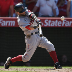 Boston Red Sox second baseman Dustin Pedroia hits a three-run home run against the Los Angeles Angels during the ninth inning Sunday at Angel Stadium of Anaheim.