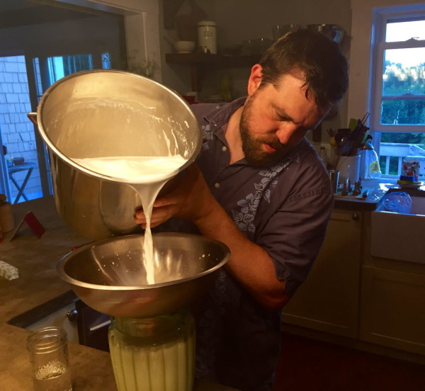 Karl Schatz pours fresh goat milk into a bucket in his kitchen at Ten Apple Farm.
