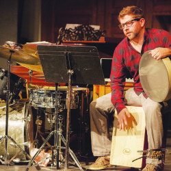 Noel Brennan multitasks with an armful of percussion instruments at a 2015 Eastport Arts Center appearance.