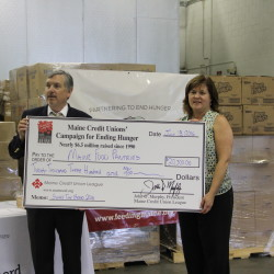 (L-R) Jon Paradise of the Maine Credit Union League and Melissa Huston of Good Shepherd Food Bank hold a check commemorating the more than $20,000 presented by the Maine Credit Unions' Campaign for Ending Hunger to food pantries across the state as part of an event to raise awareness and provide support for helping summertime hunger.