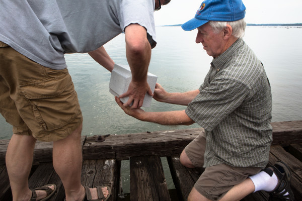 Kenneth (right) and Robert Jodrie spread their father Will''s ashes in Portland Harbor from a train trestle Friday. Will Jodrie, 93, died last week after living his whole life in Riverton.