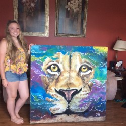 "Caeley Brown stands next to a portrait of a lion she produced in her Houlton living room recently. The self-taught artist, who is a nursing student at the University of Maine, prefers to create art for ""the pure joy of it"" and does not plan to make a career of it."