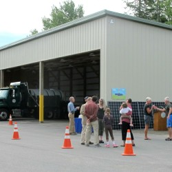 A small crowd gathers Monday morning next to a more than 200-foot-long storage building at the town's public works facility off Crooked Road.