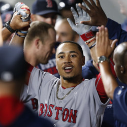 Boston Red Sox right fielder Mookie Betts celebrates in the dugout with teammates after hitting a solo home run against the Seattle Mariners during the ninth inning Monday night at Safeco Field in Seattle. Boston defeated Seattle, 2-1.