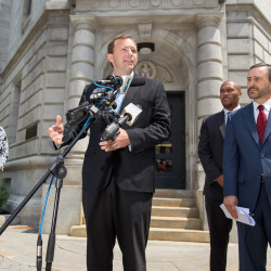 House Speaker Mark Eves (second from left) addresses reporters while wife Laura Eves (left) and David Webbert (right), his attorney, look on during a press conference on July 30, 2015, outside the U.S. District Court in Portland. Eves and Webbert filed a lawsuit against Gov. Paul LePage accusing him of blackmailing Good Will-Hinckley.