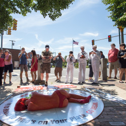 A crowd gathers to take pictures of Mysti Lee, 21, of Chicago as she lies nearly naked, painted red and wearing lobster claws, protesting the Maine Lobster Festival for PETA on Wednesday on a cardboard plate on the sidewalk at the corner of Main and Park streets in Rockland.
