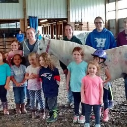 "Children and teenage volunteers who participated in one of Amy Woods Metherell's summer mini-camps in early July at the horse stable she operates, Horseplay Farm, pose for a photograph after finishing up the final event of the session, ""painting"" Henry, one of Metherell's horses, with nontoxic, washable paint. The short sessions on her stable property on the McSheffrey Road are designed to introduce young children to horses while teaching them about kindness and creativity."