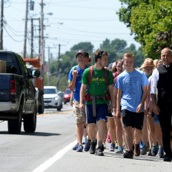 Three men who plan to be priests in Maine walked from Lewiston to Bangor to promote vocations in the Roman Catholic Diocese of Portland. Seminarians Liam Gallagher (left) and Dennis Fitts (center), along with Rev. Seamus Griesbach lead the group of teens on their walk to Bangor on Friday.