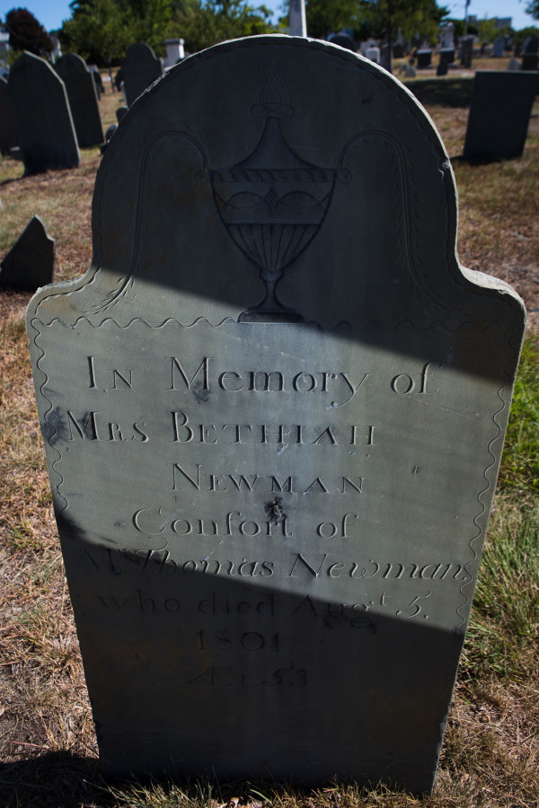 Bethiah Newman's headstone in Portland's Eastern Cemetery, dating from 1801, is the work of the city's first full-time stonecutter, Bartlett Adams. Ron Romano, who has written a new book about Adams, reflects light from a mirror on the stone to reveal Adams' fine work Monday.