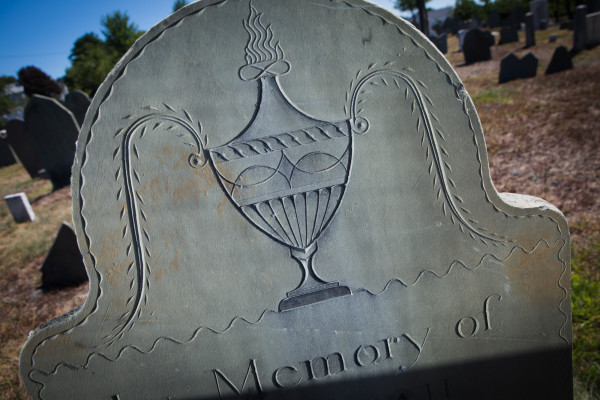 Reflected sunlight from a mirror reveals an urn carved by Bartlett Adams on a slate tombstone in Portland's Eastern Cemetery on Monday. Portland native Ron Romano has written a new book about Adams and his art.