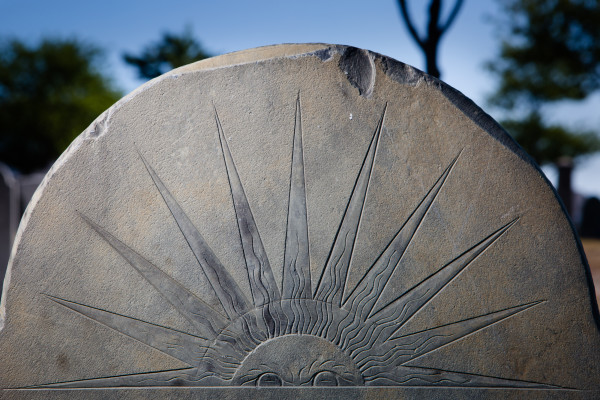 A rising sun motif, symbolizing the soul's ascension to heaven, shines on Lucy Pierce's gravestone in Portland's Eastern Cemetery on Monday. The city's first full-time stone carver, Bartlett Adams, created the image when Pierce died in 1802.