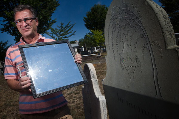 Portland writer and native Ron Romano reflects sunlight with a mirror, illuminating the work of Bartlett Adams, the city's first stone carver at the Eastern cemetery on Monday. Romano just published a book about Adams, detailing his life, art and importance in Portland's boom times of the early 19th century.