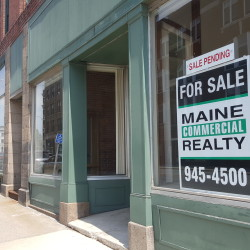 Signs were posted Wednesday in the windows of a block of downtown buildings up for sale on Exchange Street announcing their pending sale.