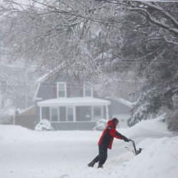 A Bangor resident clears away snow after a last winter storm dropped 11 inches on the city in March 2014.